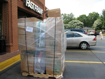 Clothes and furniture packed in boxes on shipping pallet